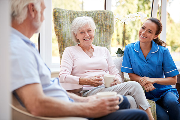 Senior-Couple-Sitting-In-Chair-And-Talking-With-Nurse-In-Retirement-Home-stock-photo-small